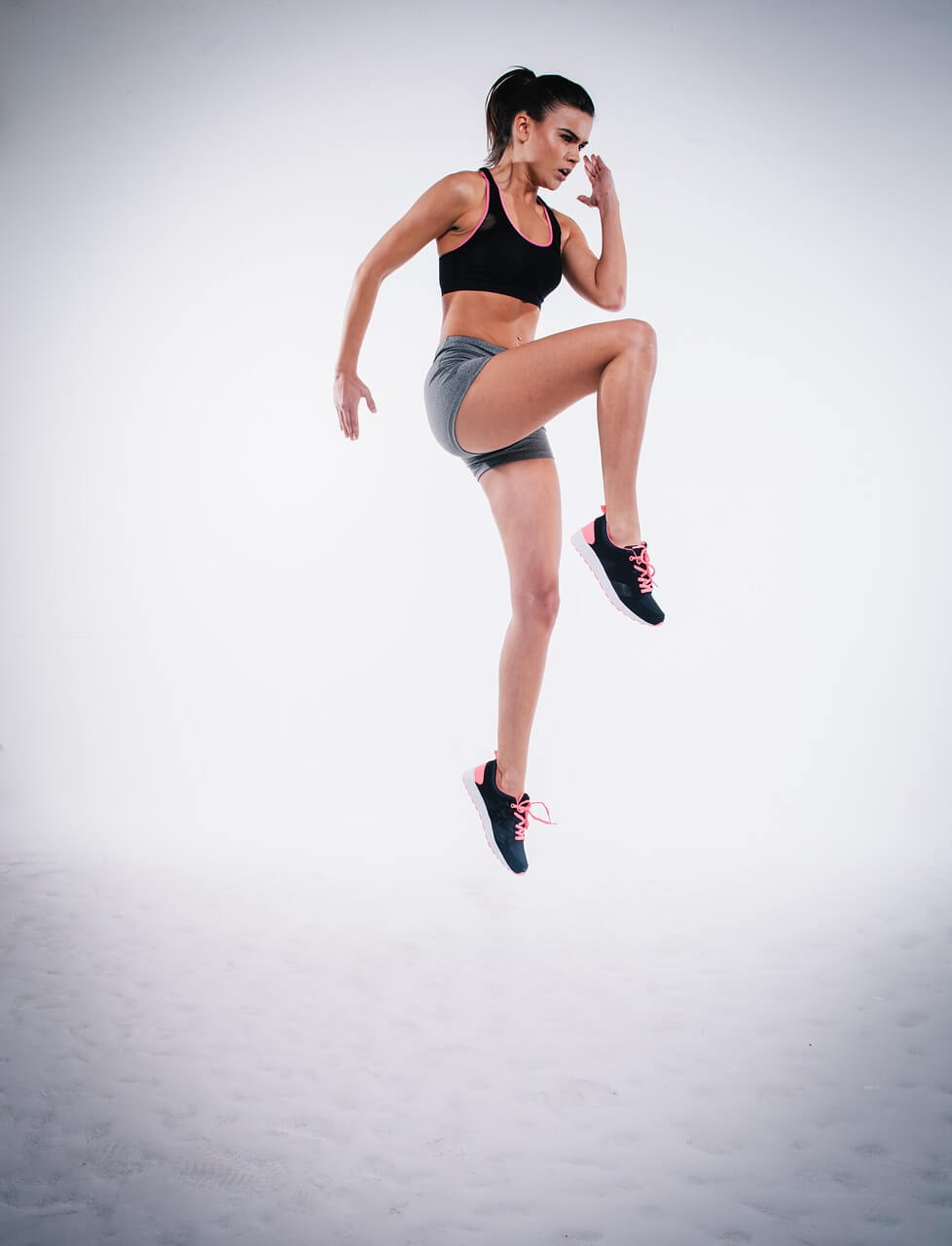 mujer en ropa de ejercicios brincando en una pierna