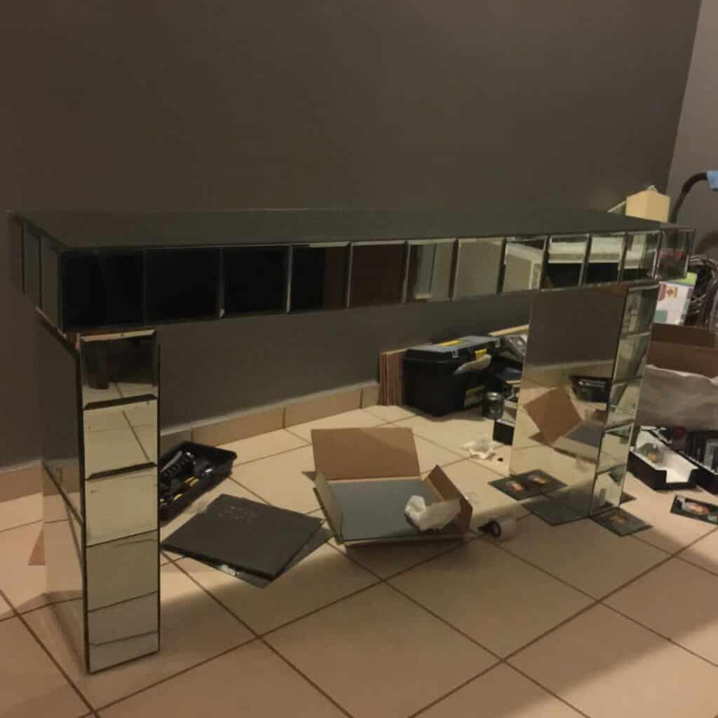 consola de espejos casi terminada y lozas de espejo se ven en el piso puestas