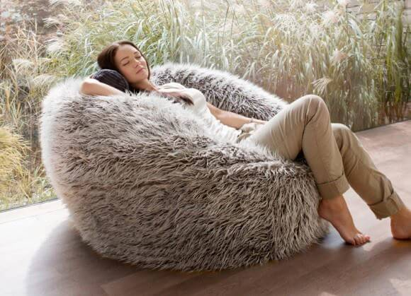 woman laying on a beige furry beanbag
