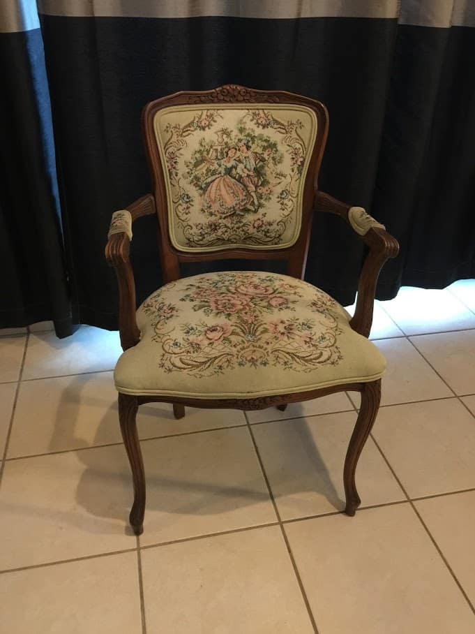 small victorian arm chair in front of a black curtain