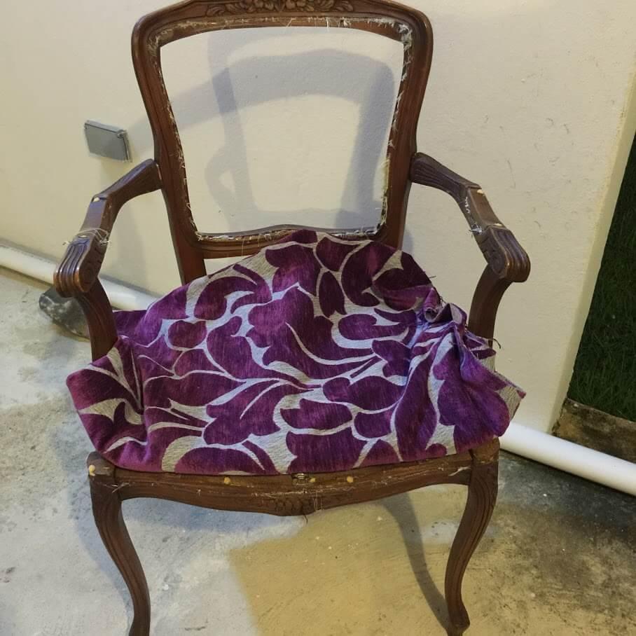 tela de tapizar con estampado color violeta y gris sobre una butaca victoriana pequeña