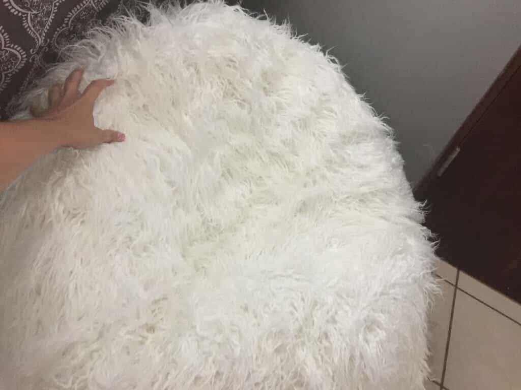 hand touching a white furry beanbag