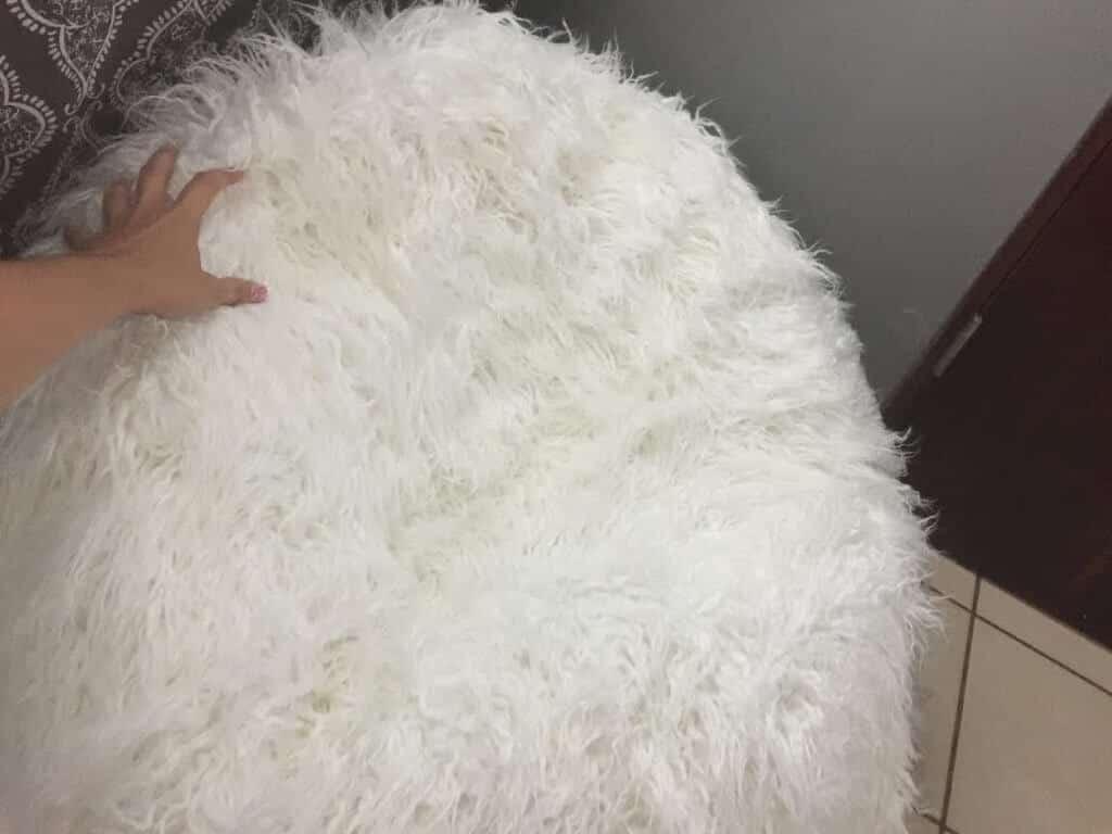 hand touching a white furry beanbag
