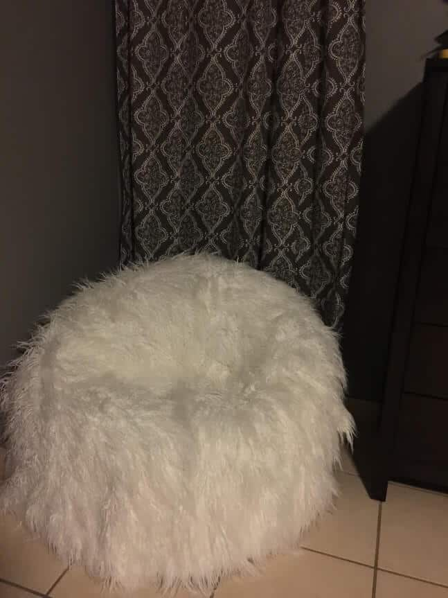 white furry bean bag behind a curtain