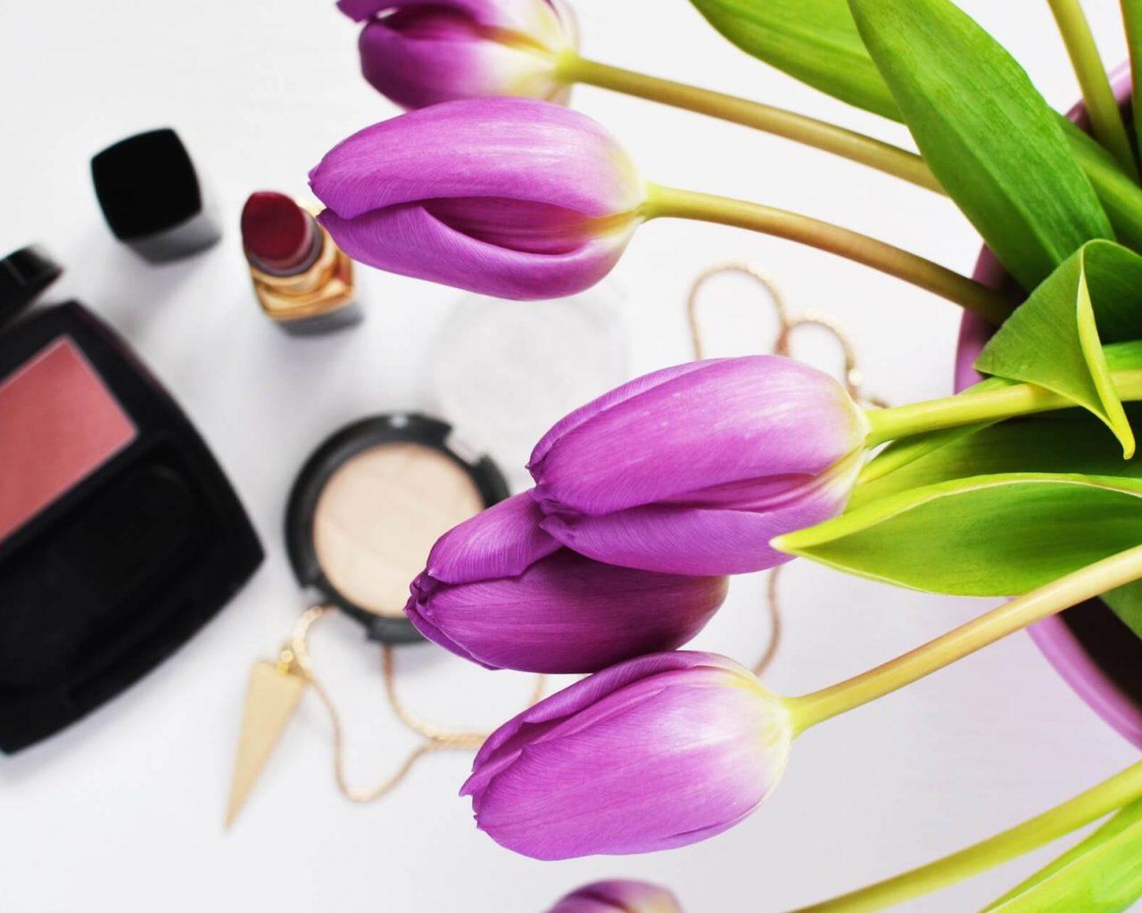 tulipanes color violeta al lado de productos de maquillaje para ilustrar cuando caduca el maquillaje