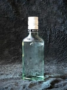 Bottle of Puerto Rican Bacardi rum photographed in a furry gray background.