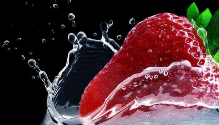 fresa cayendo al agua en imagen para un artículo sobre ideas de meriendas saludables