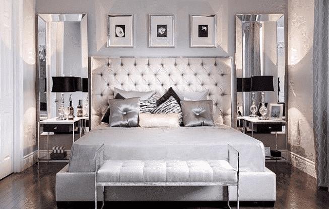 glamorosa habitación con una cama en tonos plateados y mesas de noche en espejo
