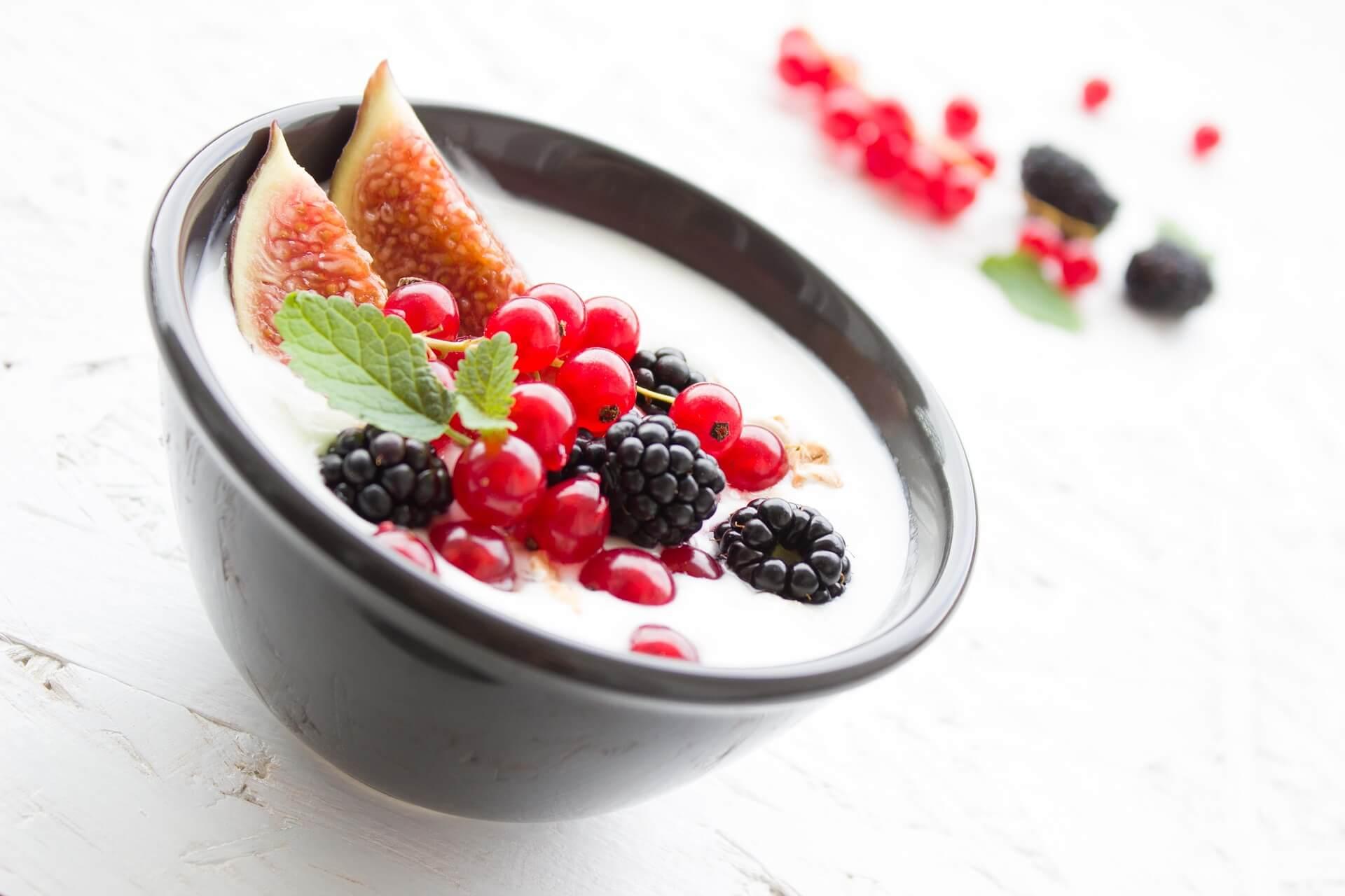plato negro con yogur con cerezas