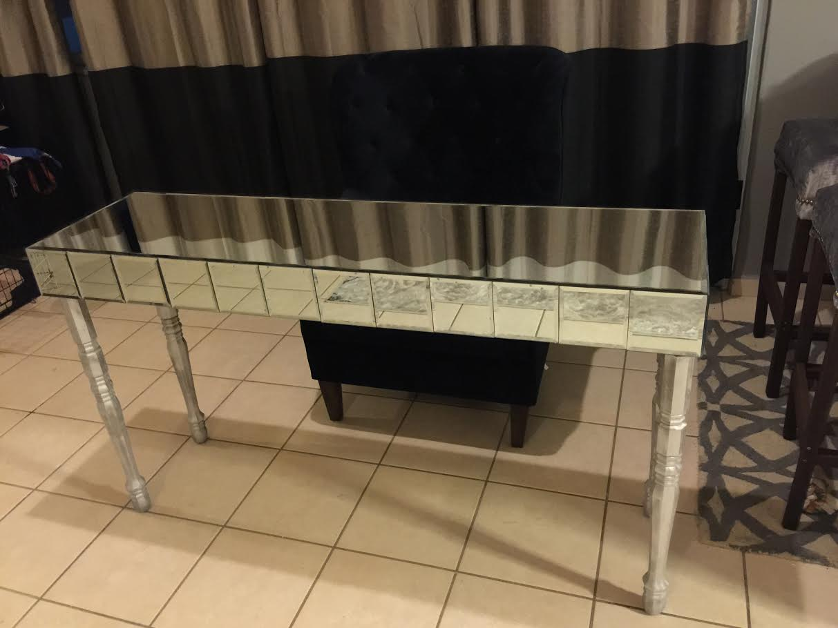 thin, mirrored table with long silver legs