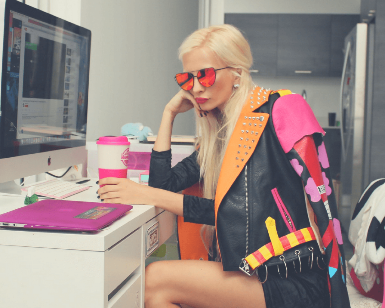 blogger sentada frente a un escritorio con taza de café en mano