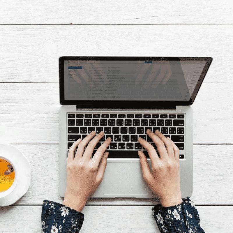 manos femeninas escribiendo sobre teclado de una computadora portátil