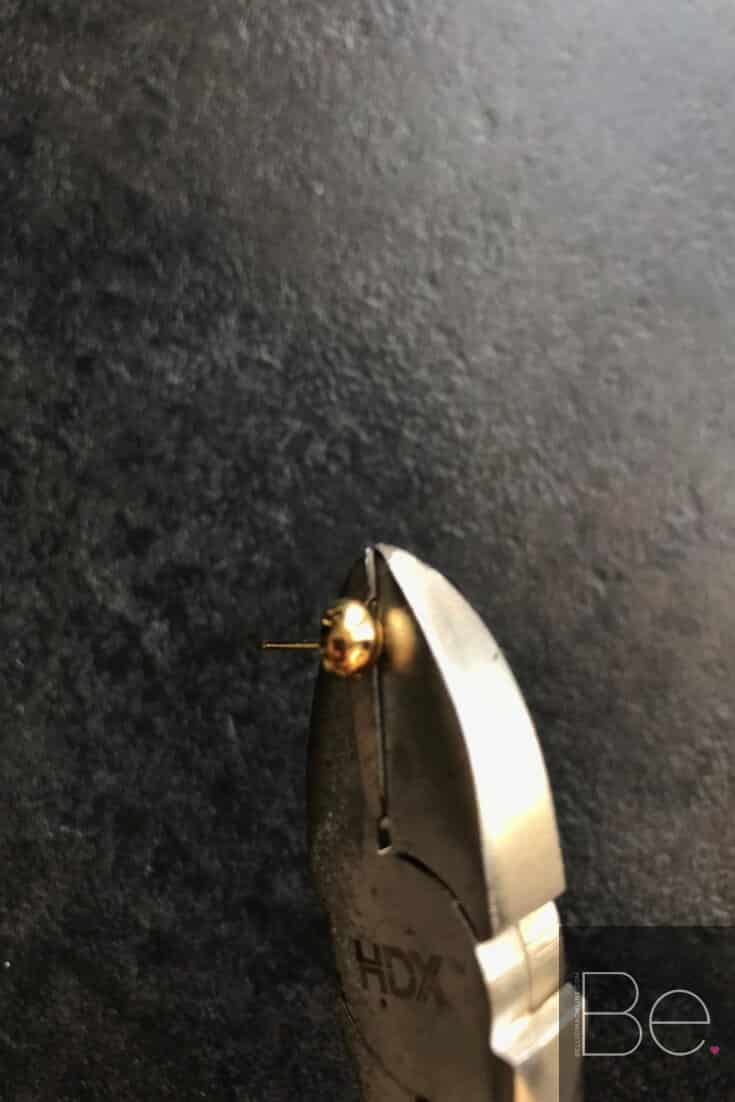 cutting pliers cutting a part of a gold earring