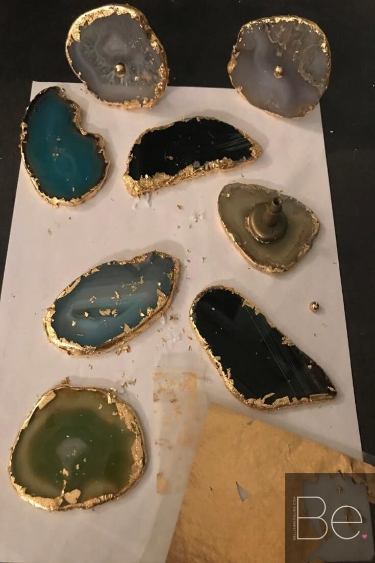 agate slices of different colors being applied gold leaf